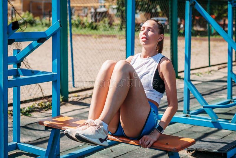 Junge schöne athletische Frau rüttelt Presse auf Sportplatz lizenzfreie stockfotos