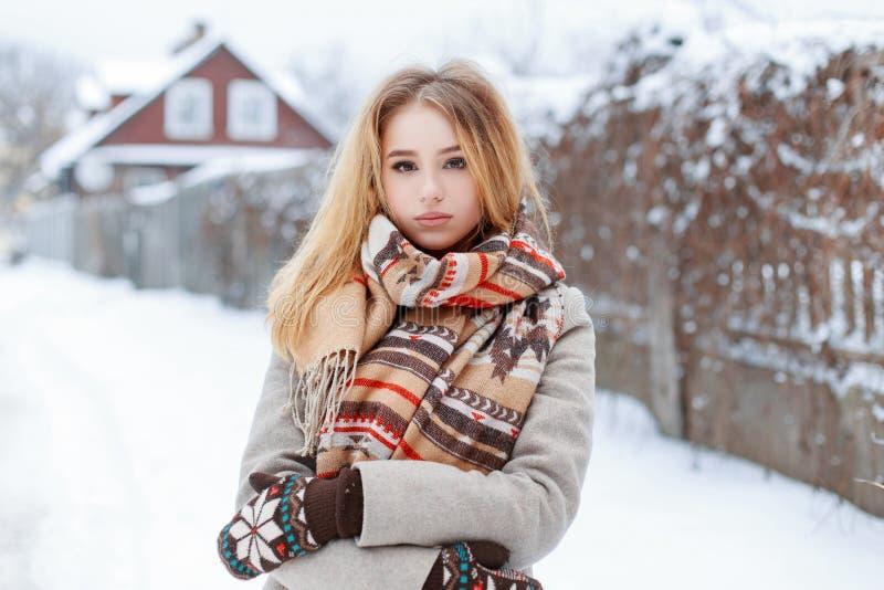 Junge schöne attraktive ländliche Frau in einem grauen Mantel der Weinlese in den woolen Handschuhen in einem stilvollen warmen S stockbild