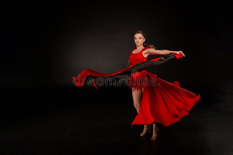 Junge schöne Bauchtänzerin, die exotischen Tanz im roten Flatternkleid perfoming ist stockbilder