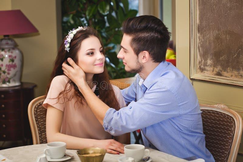 Junge schöne bezauberte Paare, die an einem Tisch in einem Café sitzen lizenzfreie stockfotos