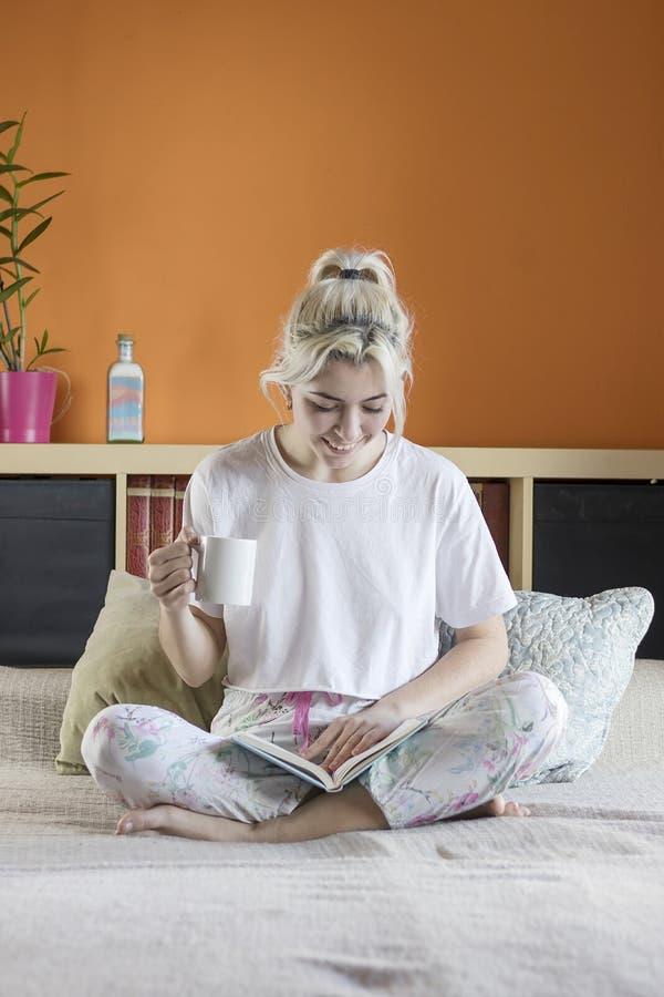 Junge schöne blond-haarige Frau sitzt auf Bett mit einem Cu lizenzfreie stockfotografie