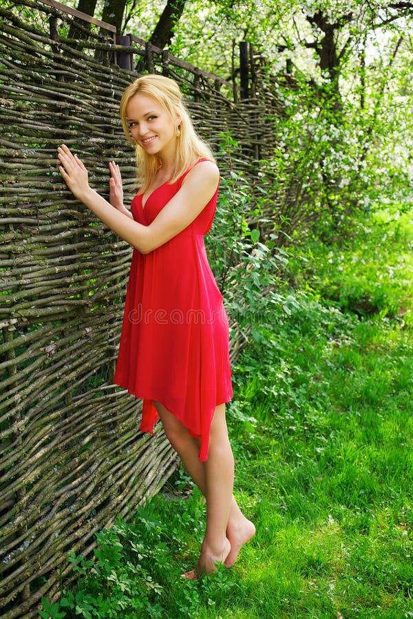 Junge schöne blonde Frau in einem roten Kleid lizenzfreie stockfotos