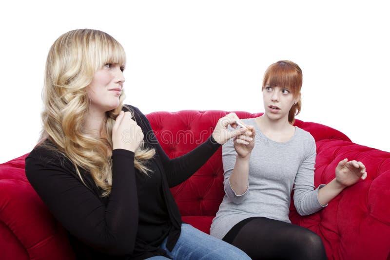 Junge schöne blonde und rote behaarte Mädchen erhalten Zigarette weg ein lizenzfreies stockfoto