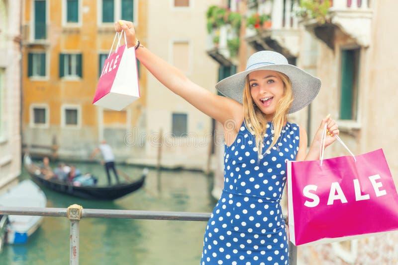 Junge schöne Blondine in der Mitte von Venedig mit Einkaufstaschen und im Vergnügen des Kaufens Mode-Modell gir Italien punktiert lizenzfreie stockfotos