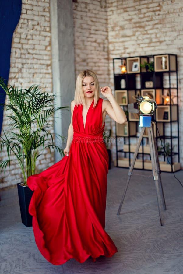 Junge schöne Blondine des Porträts im roten Abendkleid Dachboden in der Innenfotoaufnahmefrau im Abendkleid in der Bewegung stockfoto