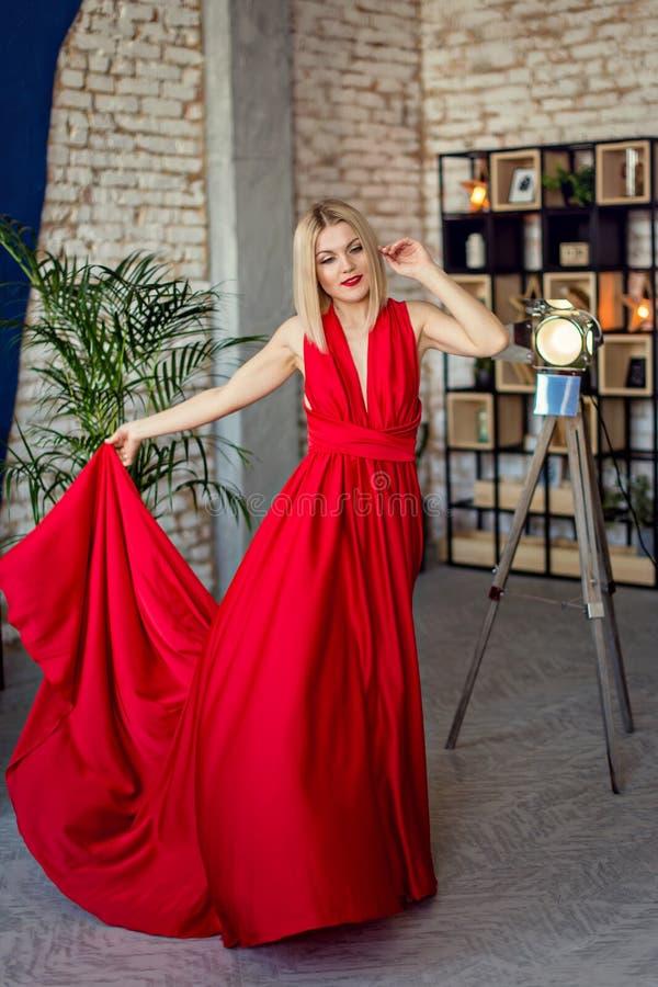 Junge schöne Blondine des Porträts im roten Abendkleid im Dachbodeninnenraum stockfoto