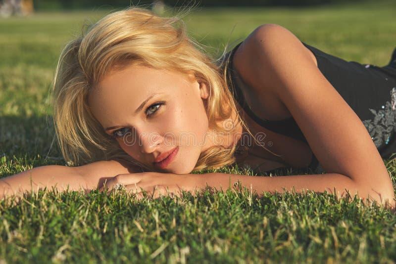 Junge schöne Blondine, die auf einer Wiese sich entspannen lizenzfreie stockfotografie