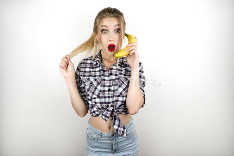 Junge schöne Blondine, welche die modischen karierten Hemd- und Denimkurzen hosen halten Banane wie ein Telefon lokalisiert trage stockfoto