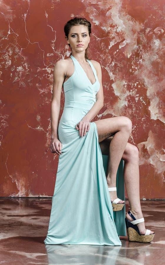 Junge schöne braunhaarige Frau im Blaulichtseidenkleid mit offenen Schultern und ein langer Rock und Sandalen lizenzfreies stockbild