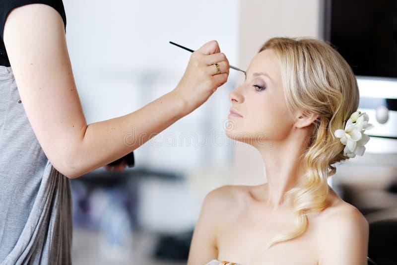 Junge schöne Braut, die Hochzeitsverfassung anwendet lizenzfreies stockfoto