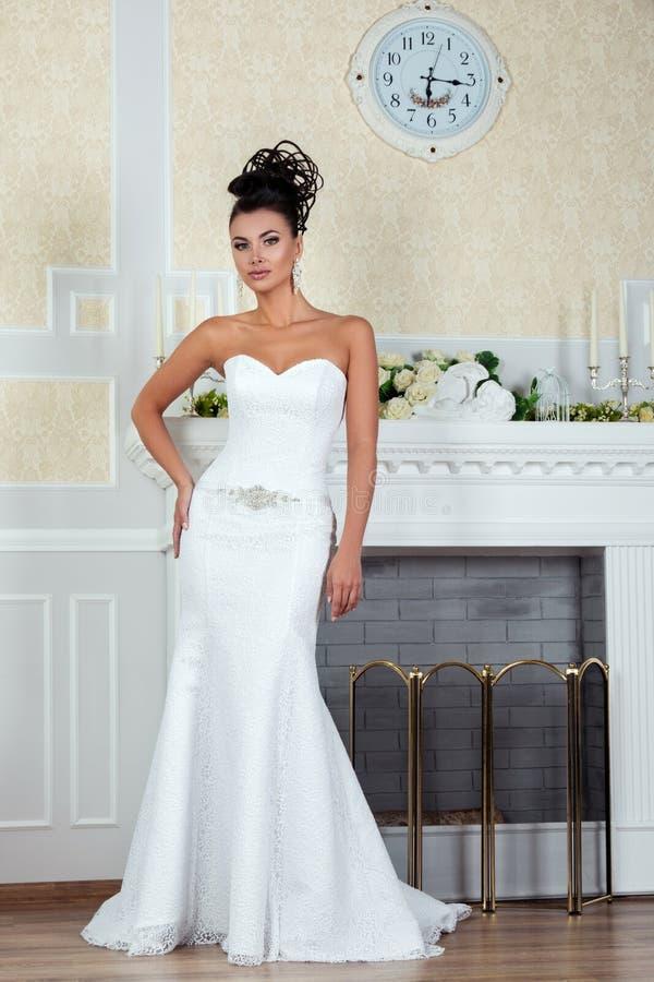 Junge schöne Braut, die nahen Kamin steht stockfotos
