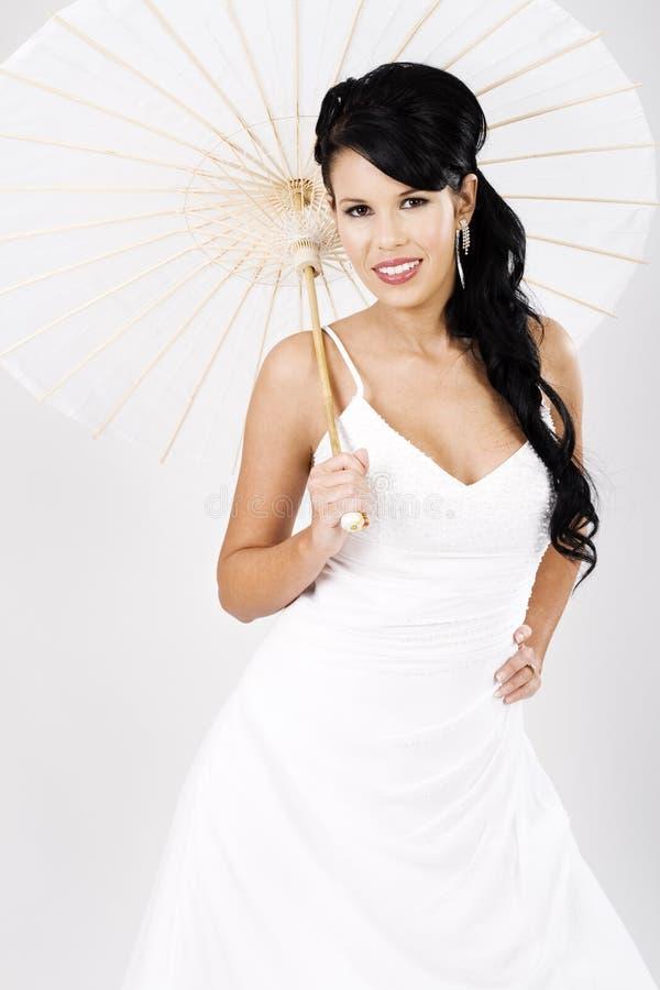 Junge schöne Braut mit weißem Regenschirm stockfoto
