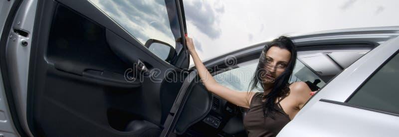 Junge schöne brunette Frauenoffene tür des Kraftfahrzeugs sitzend innerhalb des Autos lizenzfreie stockfotografie