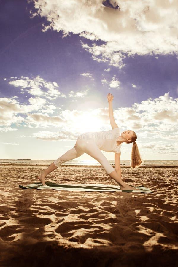 Junge schöne dünne Frau übt Yoga auf dem Strand an den sunris lizenzfreie stockfotografie
