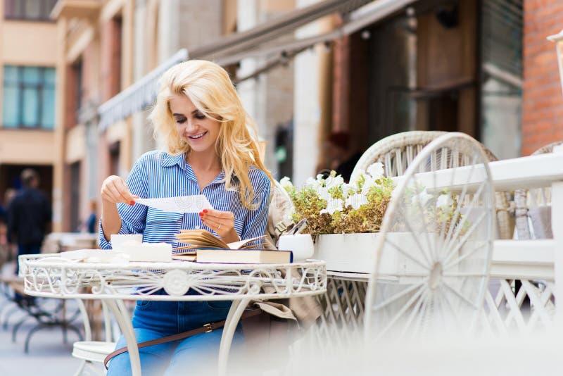 Junge schöne Dame mit erstaunlicher heller Lächelnlesebuchstabemitteilung, beim Sitzen in der Caféstange in der Frischluft, lizenzfreie stockfotos