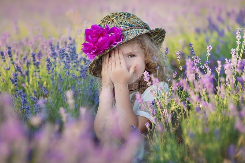 Junge schöne Damenmutter mit der reizenden Tochter, die auf das Lavendelfeld an einem Wochenendentag in den wunderbaren Kleidern  stockfotografie