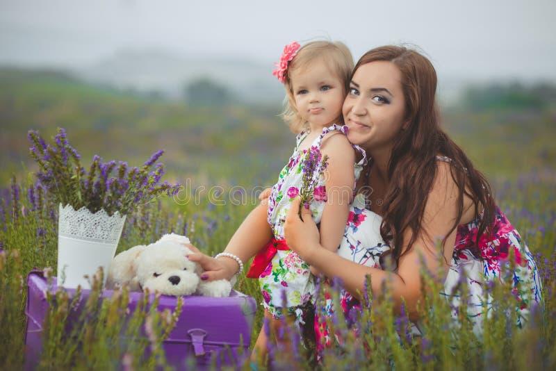 Junge schöne Damenmutter mit der reizenden Tochter, die auf das Lavendelfeld an einem Wochenendentag in den wunderbaren Kleidern  lizenzfreies stockbild