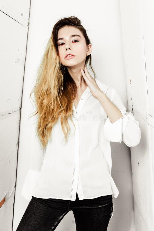Junge schöne ernste dunkelhaarige Frau des Porträts im weißen Hemd lizenzfreies stockbild