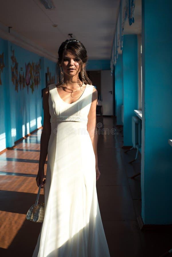 Junge schöne erstaunliche Frau, die im langen eleganten weißen Glättungskleid aufwirft innen stockbilder