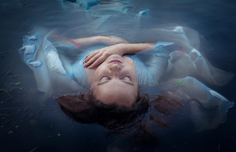 Junge schöne ertrunkene Frau im blauen Kleid, das im Wasser liegt lizenzfreies stockbild