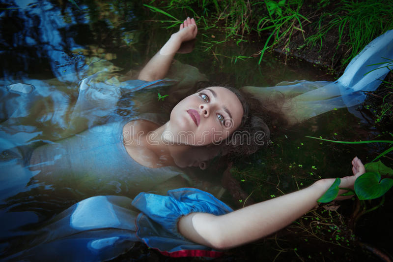 Junge schöne ertrunkene Frau im blauen Kleid, das im Wasser liegt lizenzfreie stockfotografie