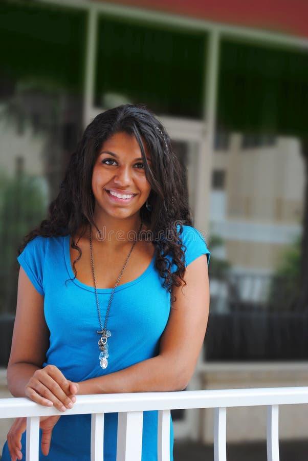 Junge schöne exotische Frau, die vom Balkon lächelt stockfotos