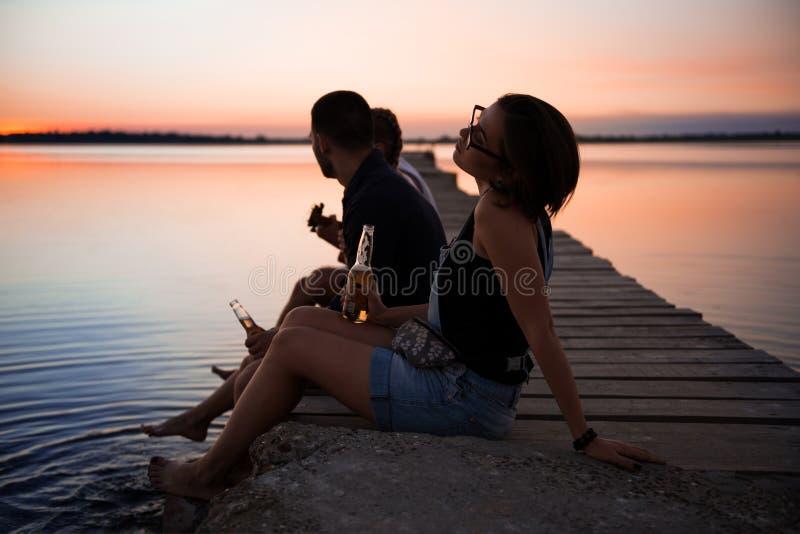 Junge schöne Firma von den Freunden, die an der Küste während des Sonnenaufgangs stillstehen lizenzfreies stockbild
