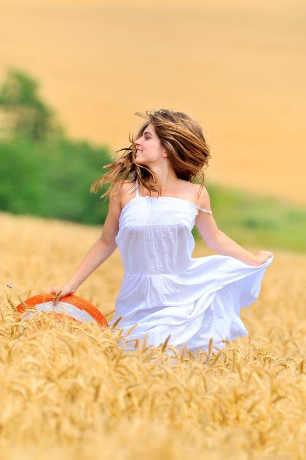 Junge schöne Frau auf dem goldenen Weizengebiet stockbilder