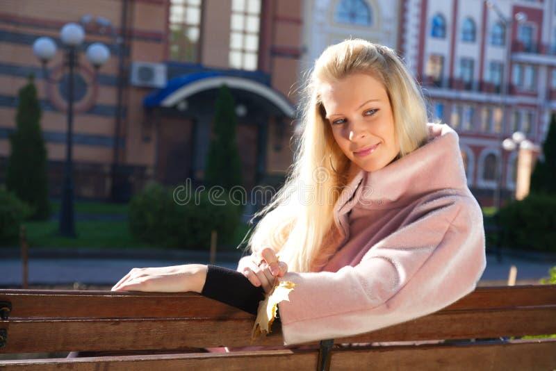 Junge schöne Frau, die auf der Bank sitzt stockfotos