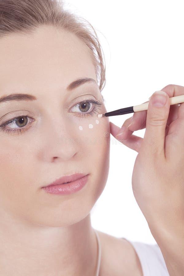 Junge schöne Frau, die concealer auf Gesicht anwendet lizenzfreie stockbilder