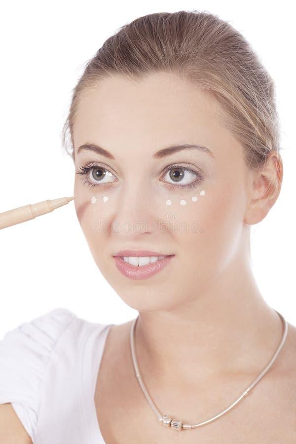 Junge schöne Frau, die concealer auf Gesicht anwendet lizenzfreies stockbild