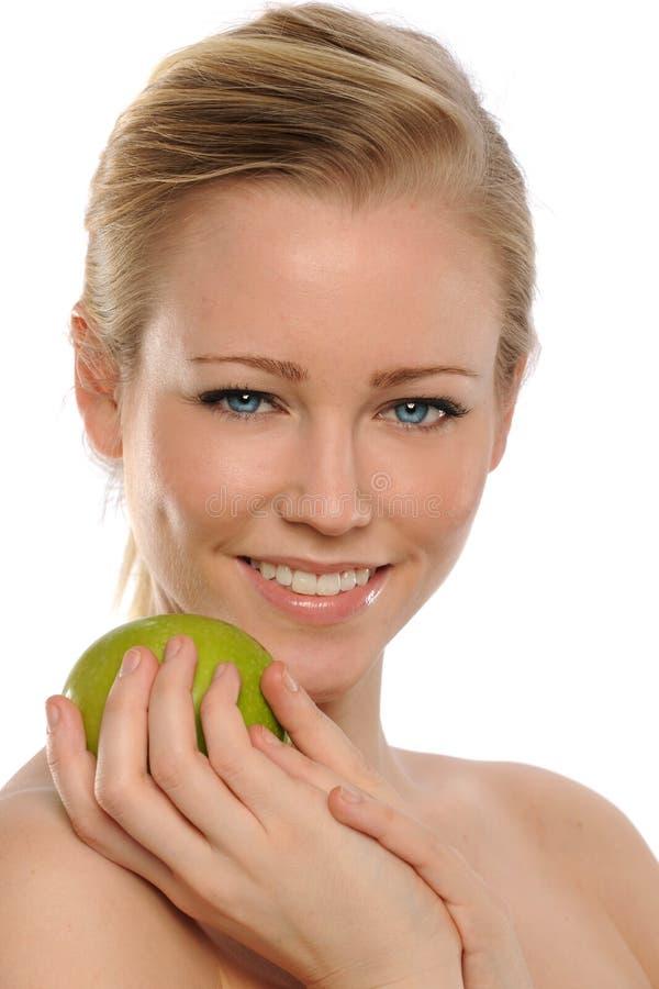 Junge schöne Frau, die einen grünen Apfel anhält lizenzfreie stockfotografie