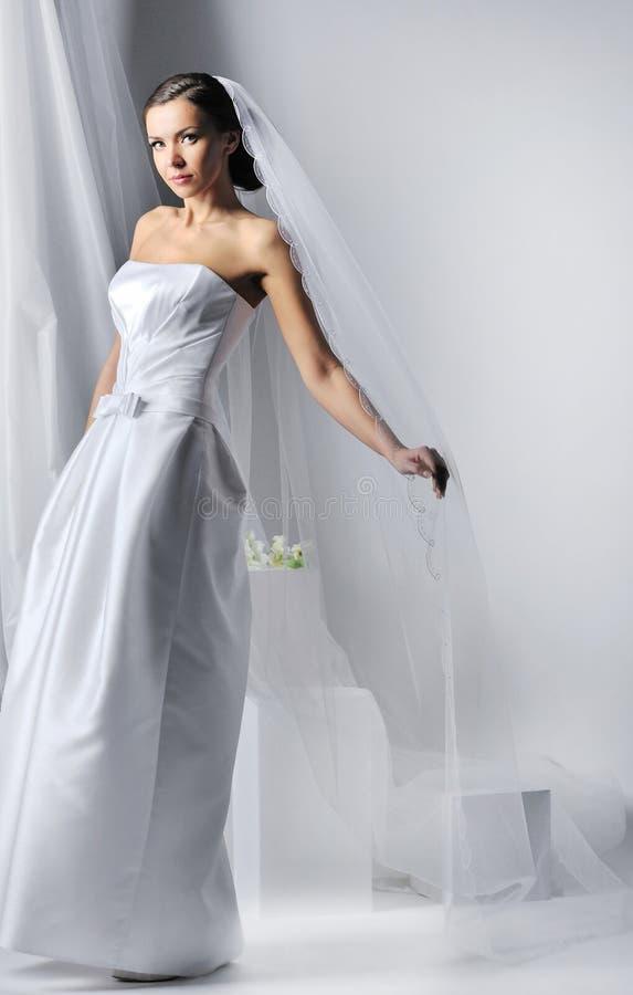 Junge schöne Frau, die luxuriöses Hochzeitskleid trägt lizenzfreies stockbild