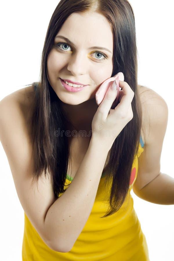 Junge schöne Frau, die Puder anwendet stockfotografie