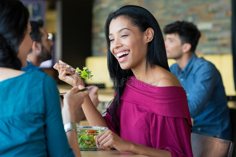 Junge schöne Frau, die Salat isst stockfoto