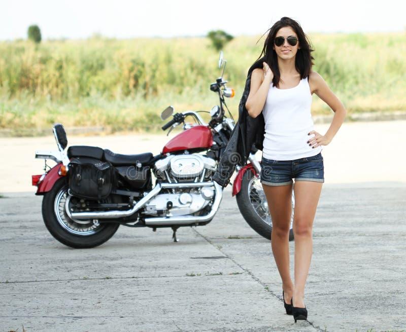 Junge schöne Frau, die von einem Motorrad geht lizenzfreies stockbild