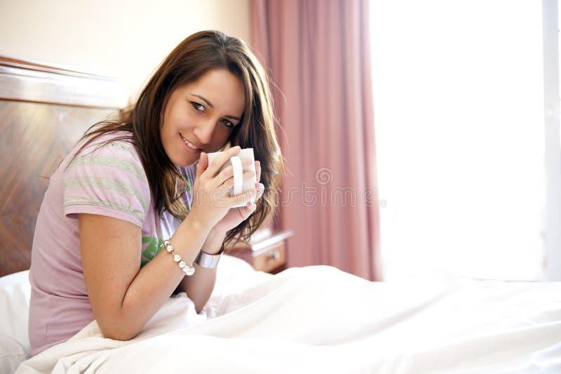Junge schöne Frau im Bett lizenzfreie stockfotografie