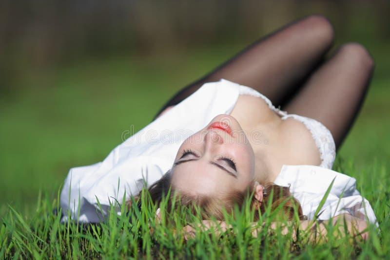 Junge schöne Frau im Gras im Freien lizenzfreie stockbilder