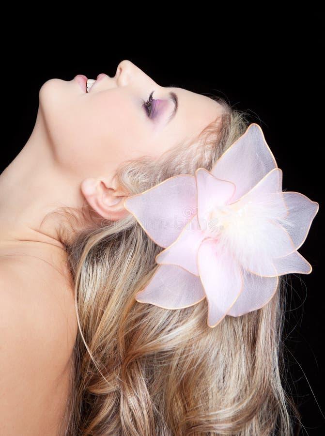 Junge schöne Frau mit Blume im blonden Haar lizenzfreie stockbilder