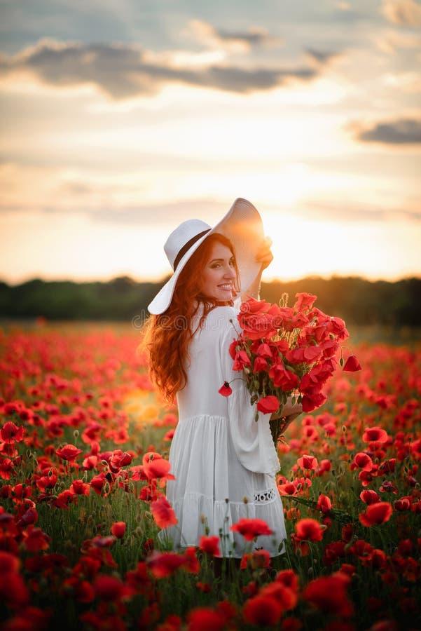 Junge schöne Frau mit Blumenstrauß von roten Mohnblumenständen auf dem geblühten Gebiet bei Sonnenuntergang stockfoto