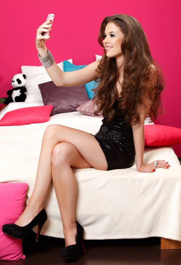 Junge schöne Frau nimmt Fotos mit ihrem Telefon stockfotografie