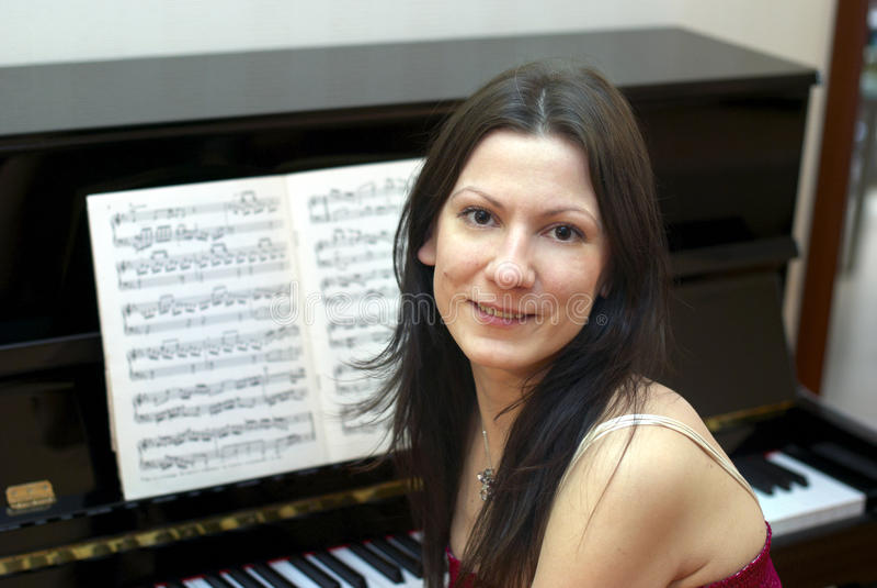 Junge schöne Frau am schwarzen Klavier stockfotos