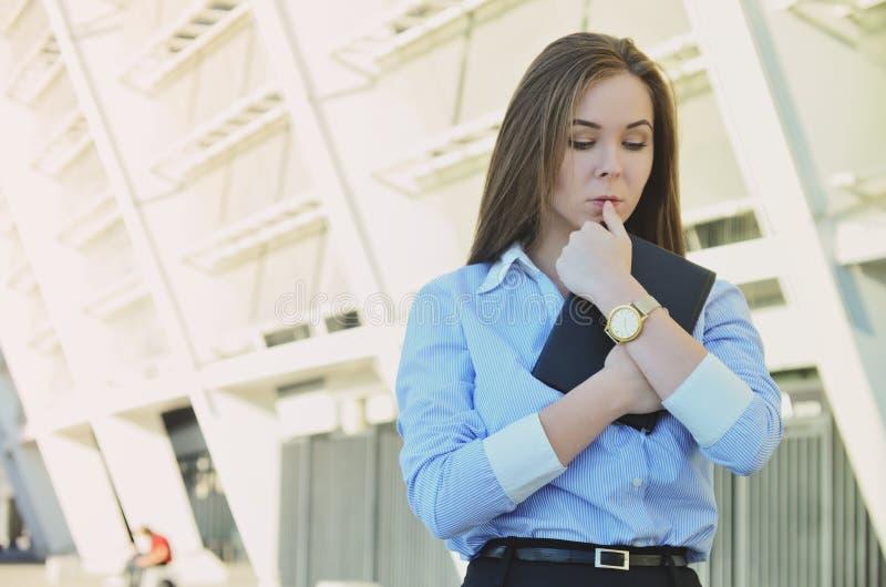 Junge schöne Geschäftsdame in der Bürokleidung, die ein Notizbuch in ihren Händen hält stockbild