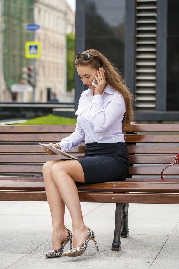 Junge schöne Geschäftsfrau, die auf einer Bank im sonnigen c sitzt lizenzfreie stockfotos
