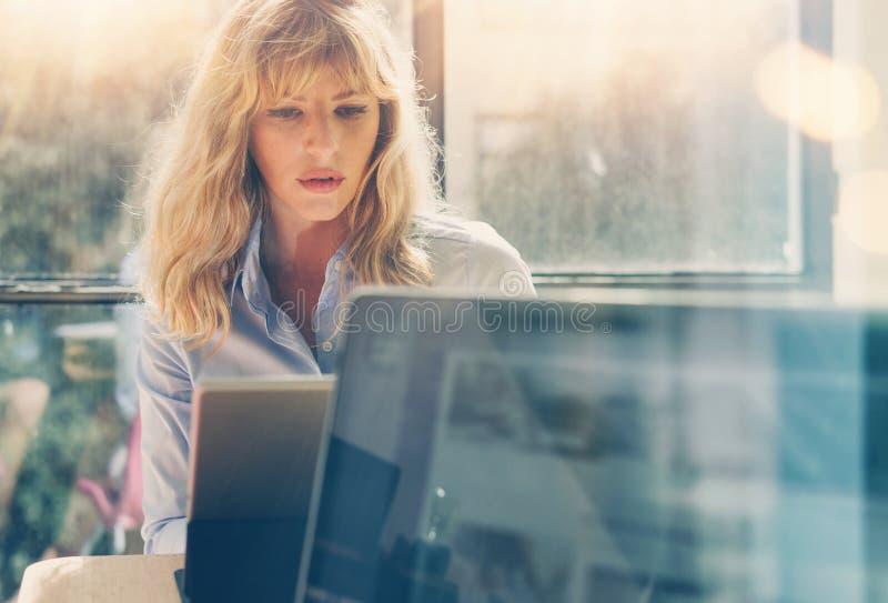 Junge schöne Geschäftsfrau, die an der Laptop-Computer im sonnigen Büro arbeitet Panoramische Fenster auf unscharfem Hintergrund stockbild