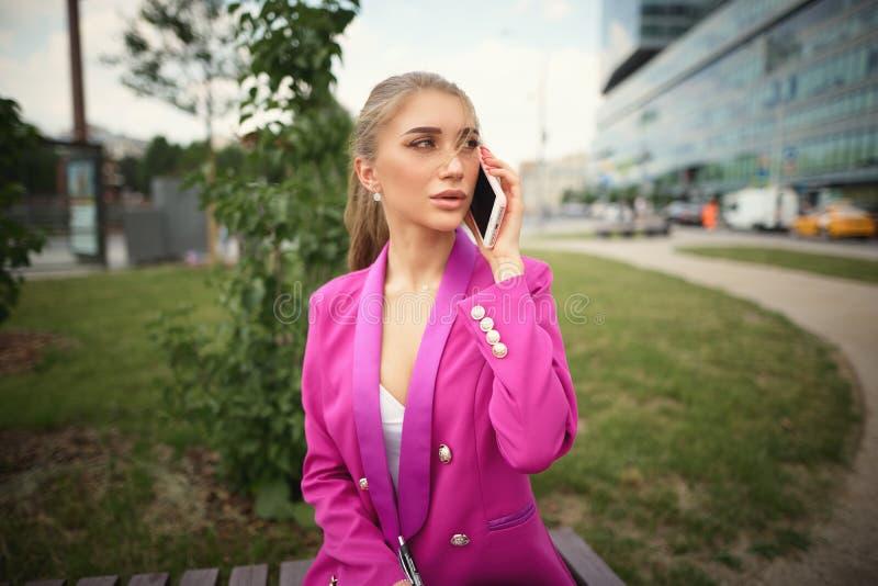 Junge schöne Geschäftsfrau, die am Telefon spricht Die goldene Taste oder Erreichen f?r den Himmel zum Eigenheimbesitze lizenzfreies stockbild