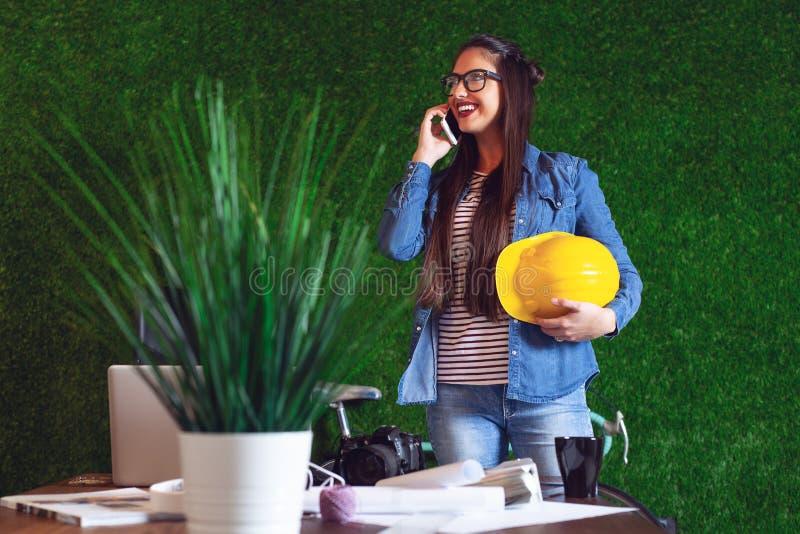 Junge schöne Geschäftsfrau, die am Telefon spricht und an Tabelle in einem modernen Büro - Bild arbeitet lizenzfreie stockfotografie