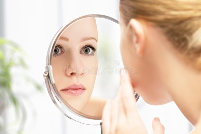Junge schöne gesunde Frau und Reflexion im Spiegel stockfotografie
