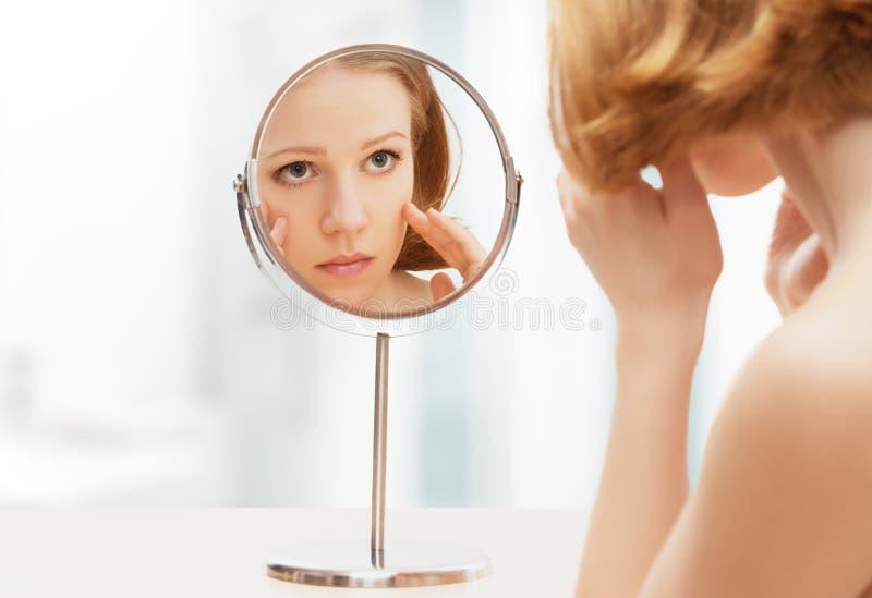 Junge schöne gesunde Frau und Reflexion im Spiegel lizenzfreie stockfotos
