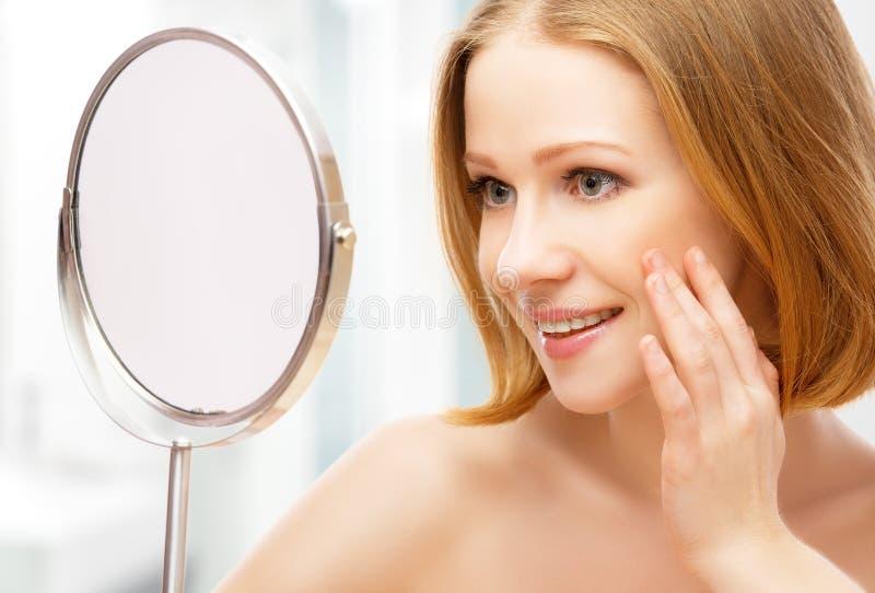 Junge schöne gesunde Frau und Reflexion im Spiegel lizenzfreies stockbild